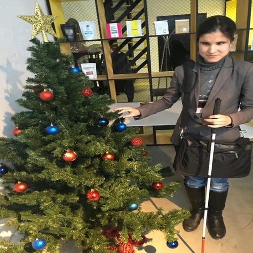 Алия Нуруллина с тростью в руке стоит возле новогодней елки, украшенной красными и синими шарами