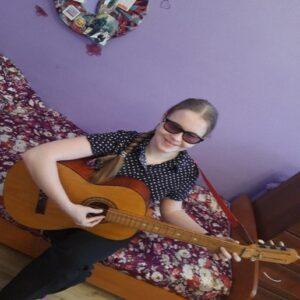 Ольга Александрова сидит на кровати, закинув ногу на ногу, и играет на гитаре