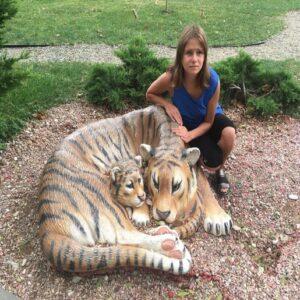 Елена Катуркина сидит на корточках возле скульптуры в виде тигрицы с тигренком, руки Елены лежат на спине тигрицы