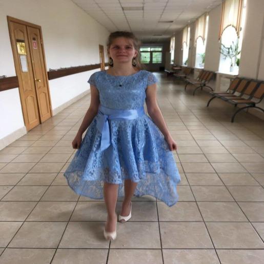 Елена Катуркина идет по коридору, на ней голубое платье с атласным бантом на поясе