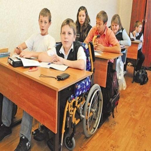 Школьный класс, рядом с обычным ребенком за партой сидит ребенок в инвалидной коляске
