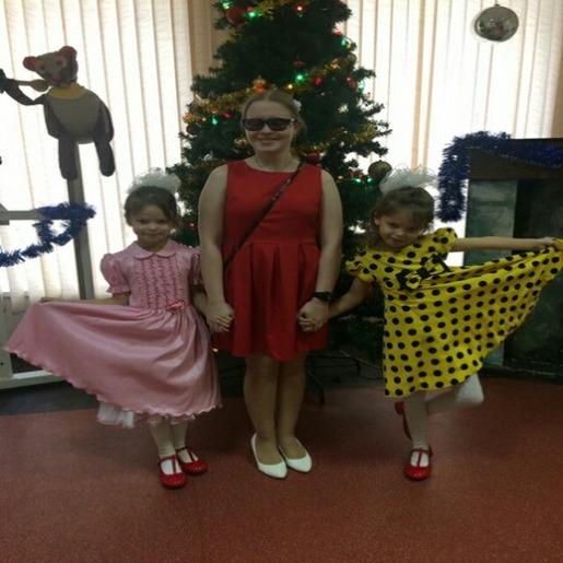 Улыбающаяся Ольга Александрова стоит перед новогодней елкой, держа за руки двух девочек