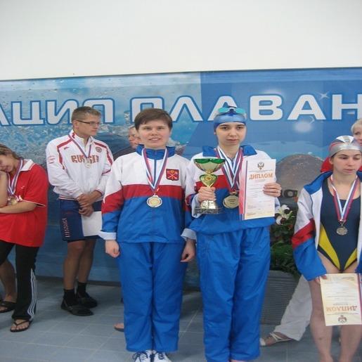 Екатерина Фаустова с группой пловцов с медалями и дипломами.