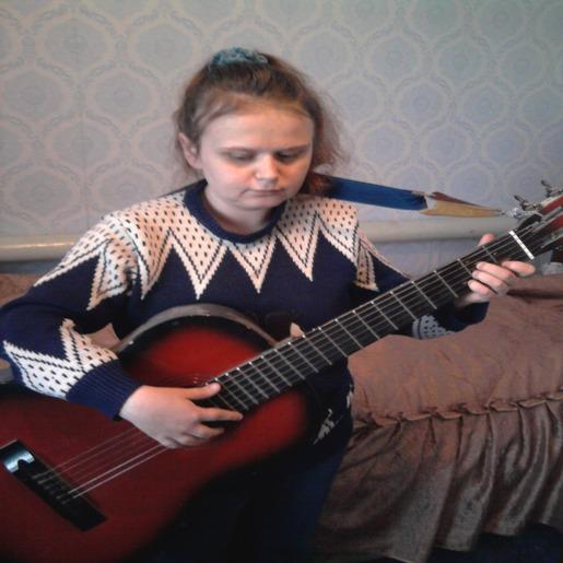 Виктория Аксенченко сидит на кровати и играет на гитаре