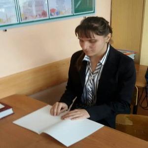 Карина Райская сидит за партой в классе, перед ней лежит тетрадь для письма по Брайлю