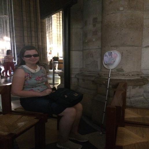 Кристина Тельпук сидит на стуле, рядом с ней у стены трость, на которую надета шляпа