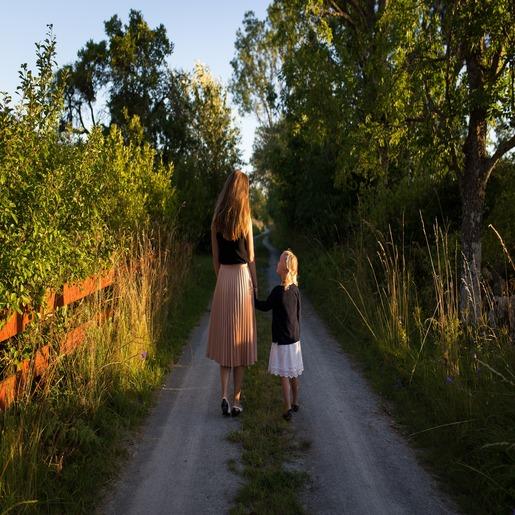 По двум расположенным вплотную тропинкам, держась за руки, идут женщина и маленькая девочка, девочка смотрит на женщину.