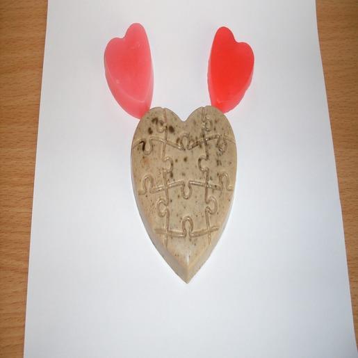 Большой кусок мыла — бежевое сердечко с рисунком в виде пазла. По краям от него — два одинаковых маленьких кусочка мыла в виде красных сердечек.