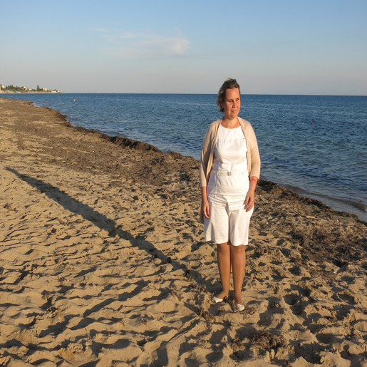 Анна Наумова стоит на песке у берега моря