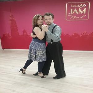Наталья Катырина с партнером танцуют танго на фоне красной стены с надписью tango jam.