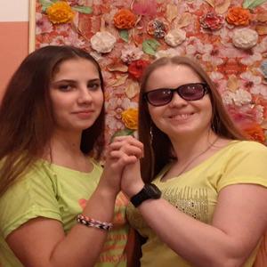 Ольга Александрова с подругой стоят, держась за руки, на фоне стены с цветами