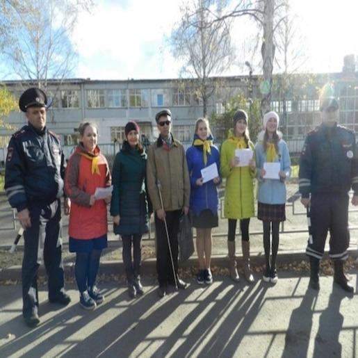Евгений Петров с группой девушек стоит на фоне невысокого здания между двух мужчин в полицейской форме