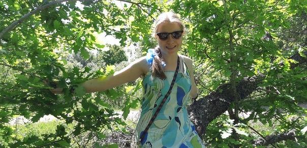 Ольга Александрова в легком платье сидит на стволе дерева на фоне листвы