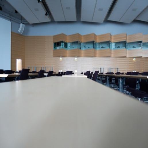Аудитория с рядами парт, стульями и экраном на стене