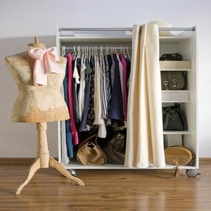Открытый шкаф с разноцветной одеждой, рядом стоит манекен, на котором повязан розовый бант