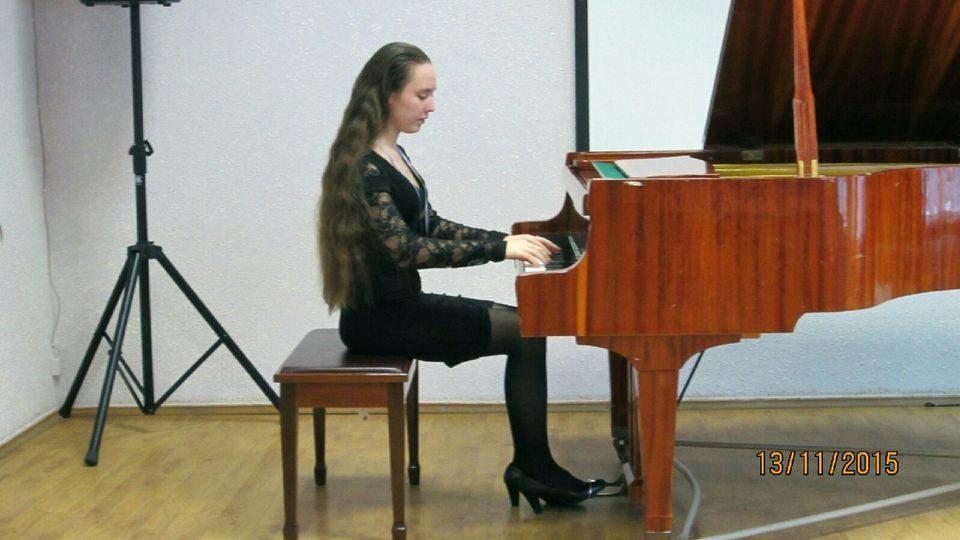 На фото Елизавета играет на рояле на концерте