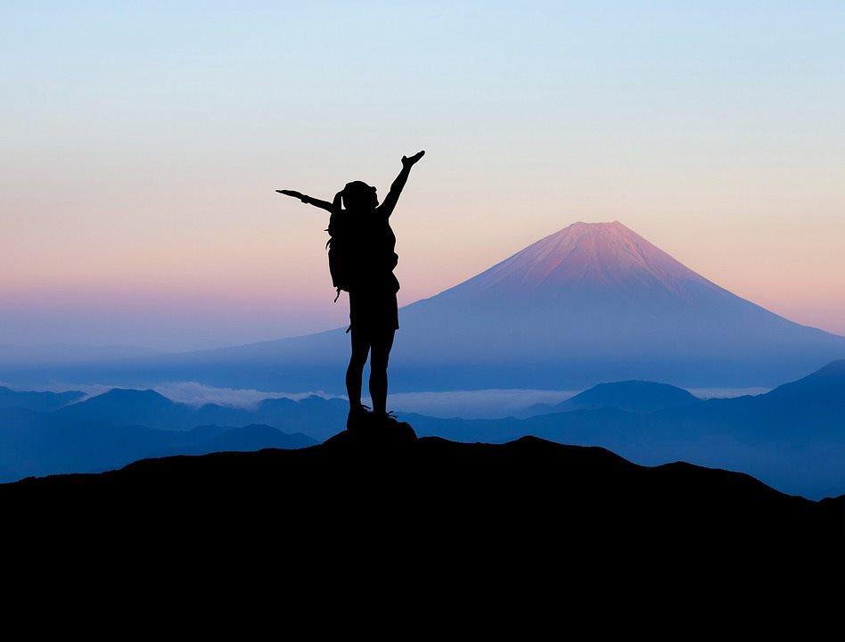 На фоне заката в горах человек с рюкзаком, подняв руки, радуется восхождению на вершину
