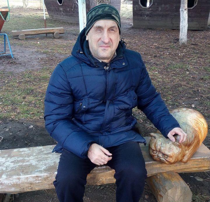 Олег сидит на скамейке возле вырезанного из дерева декоративного кота