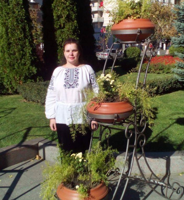 Татьяна Комарницкая стоит возле декоративной подставки с вьющимися растениями в парке