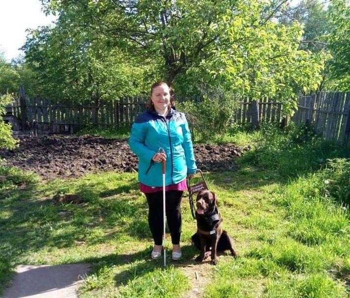 На фото на фоне природы стоит Екатерина Панкова со своей собакой
