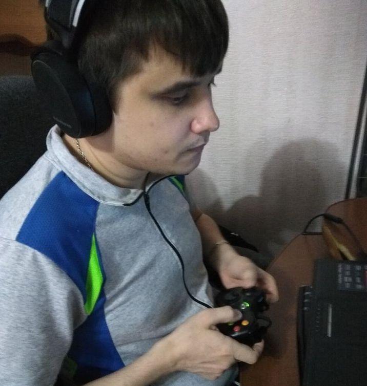 Антон Чигарев в наушниках и с джойстиком в руках перед ноутбуком