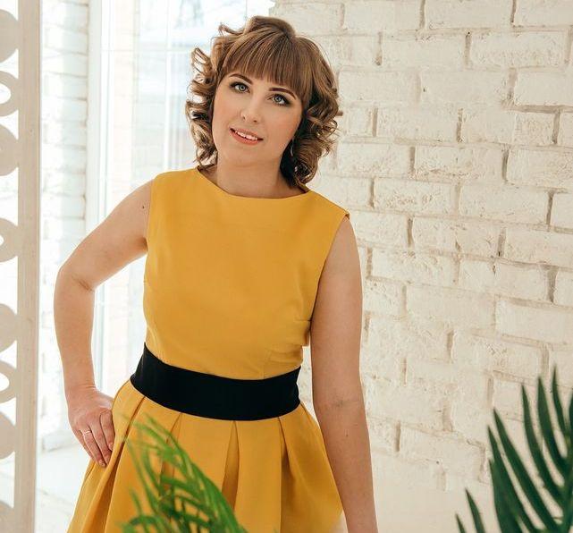 Софья Дидина в праздничном желтом платье с черным поясом.