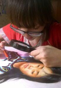 Диана Слипецкая рисует с лупой в руках