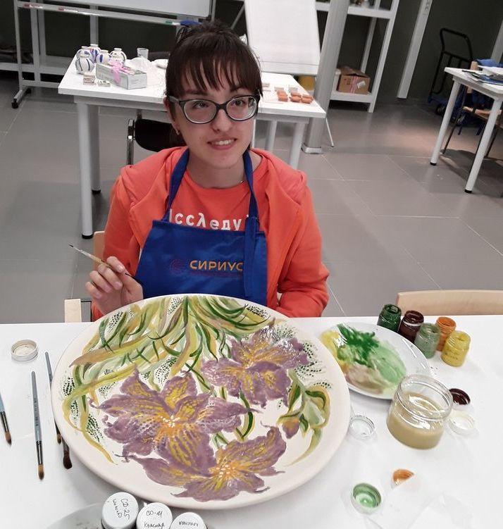 Диана Слипецкая расписывает цветами большое блюдо