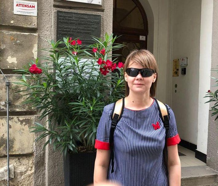 Елена Сичкар стоит возле входа с подвесной вазой с цветами
