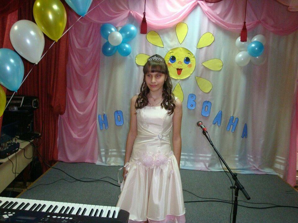 Карина Райская на празднично украшенной школьной сцене