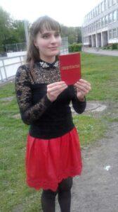 Карина Райская на школьном дворе с красным дипломом в руках