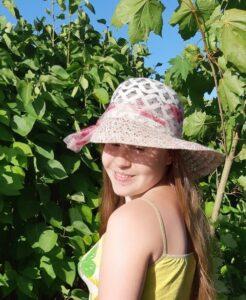 Ольга Сереброва в летней шляпке на фоне зелени