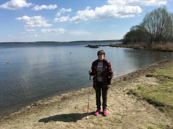 Маргарита Мельникова стоит с тростью на берегу реки