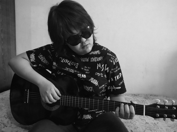 Девушка с короткой стрижкой, в черных очках - Анастасия Закон - играет на гитаре