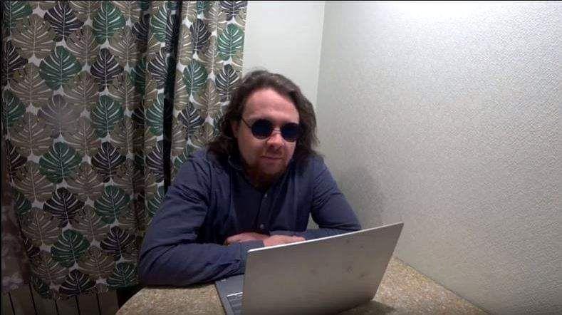 Илья Овсянников сидит за столом, работая с ноутбуком