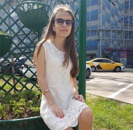 Кристина Павлова в светлом платье сидит на улице на фоне зелени