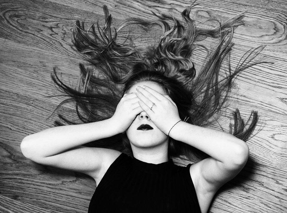 Изображение: девушка с длинными волосами лежит на полу лицом вверх, закрыв глаза руками