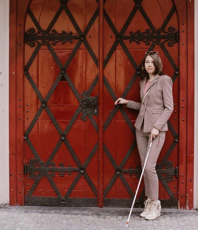Ксения Энилина стоит с тростью на фоне старинных ворот