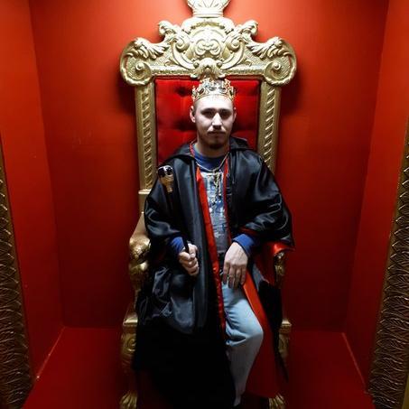 Максим Спиридонов в образе царя с короной на голове сидит на троне