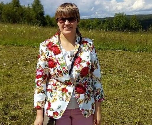 Маргарита Мельникова стоит на фоне луга