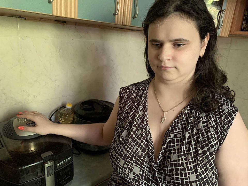 Регина стоит на кухне, держа руку на крышке мультиварки