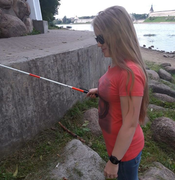 Ольга Сереброва стоит в профиль, смотрит тростью край гранитного блока