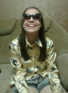 Фото улыбающейся Яны, она в нарядной блузке и темных очках