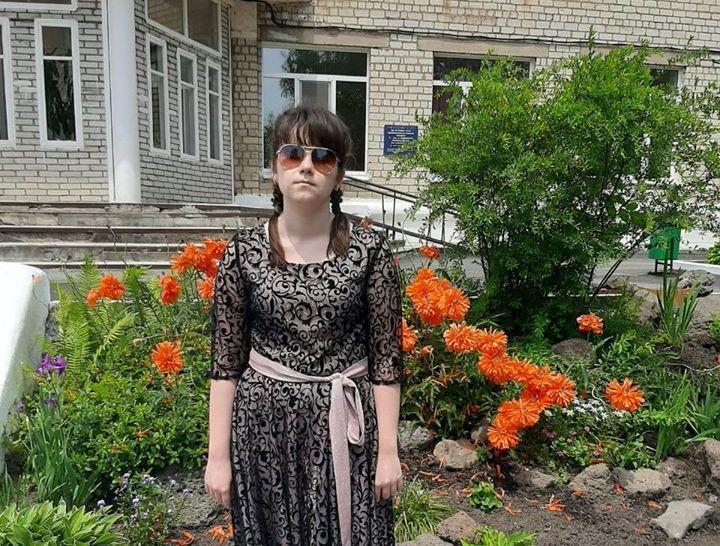 Елизавета Лошкарева стоит у школы на фоне клумбы с яркими цветами