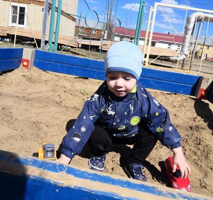 Малыш играет в песочнице