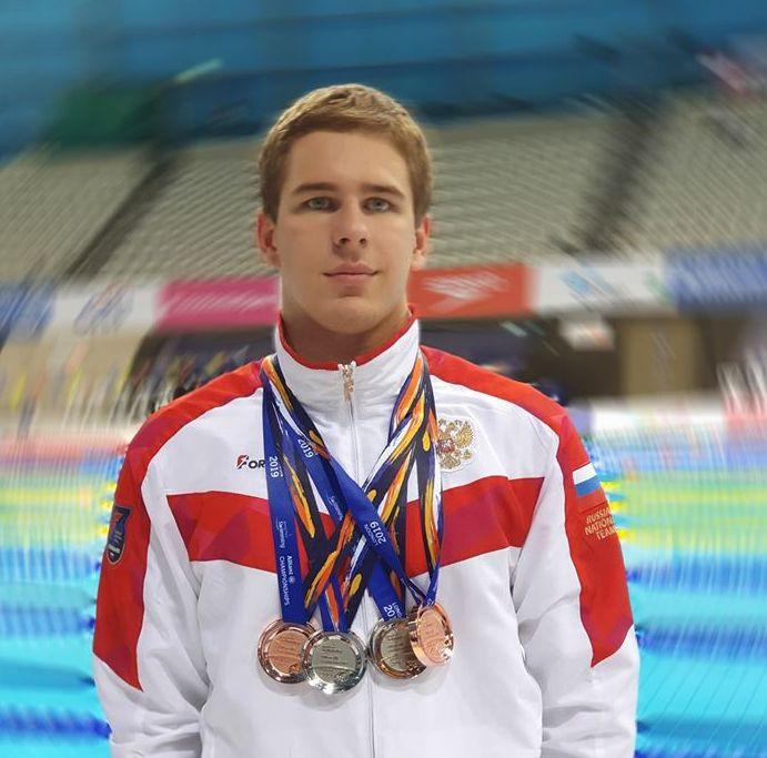 Кирилл Белоусов в спортивной форме с медалями