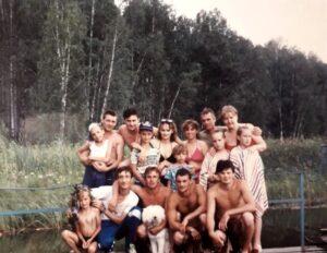 Группа молодых отдыхающих на фоне лесной речки.