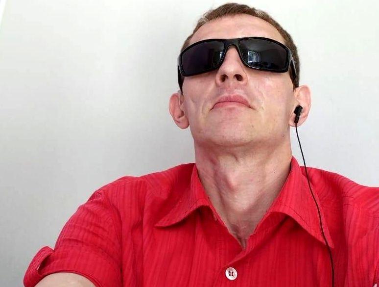 Незрячий мужчина в темных очках и красной тенниске, с наушником в левом ухе.