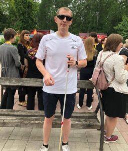 Незрячий мужчина в спортивной форме стоит возле лавочки в парке, вокруг люди.