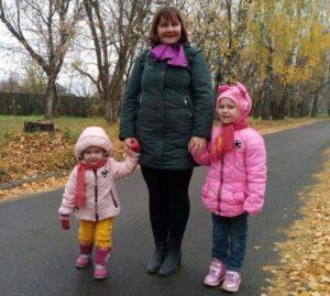 Екатерина Панкова с дочками стоят на осенней дороге
